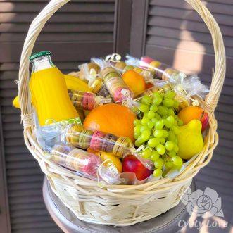 Макаруны, фрукты и напиток в корзине